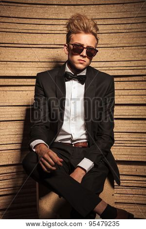 Young business man sitting with his legs crossed, looking at the camera.