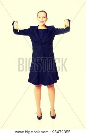 Pretty happy businesswoman pointing down