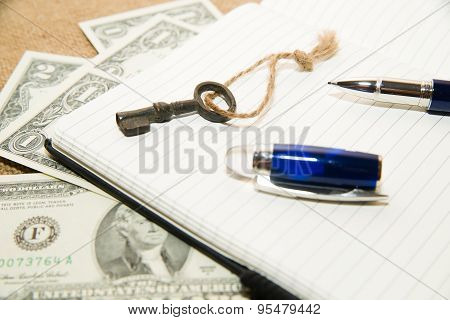 Opened Notebook, Pen, Key And Money On The Old Tissue