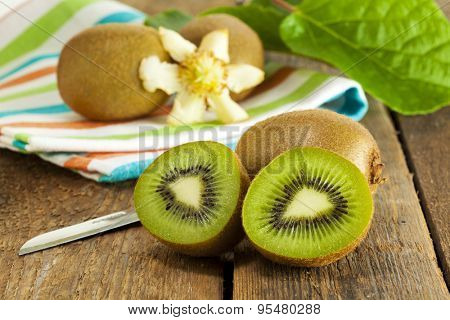Fresh Kiwi fruits with kitchen knife, towel, leaf and blossom on wooden table