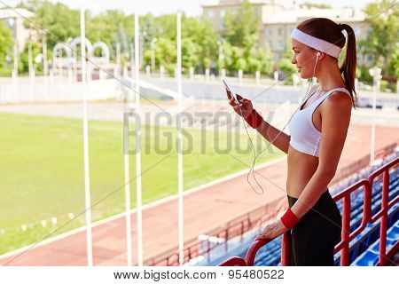Sporty girl with earphones and iphone visiting stadium