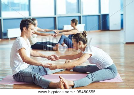 Sporty people doing exercise in pairs