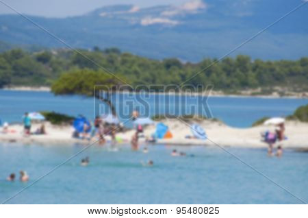 Blurred background of beach scene including colorful umbrellas and tree with a crowd of people enjoying the sunny day.