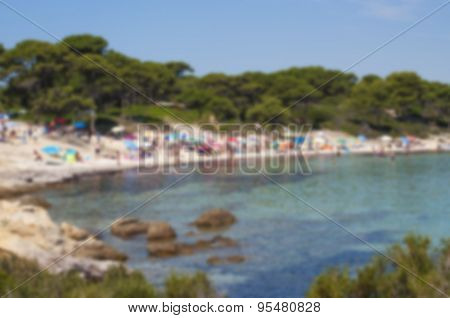 Blurred background of beach scene including colorful umbrellas with a crowd of people enjoying the sunny day.