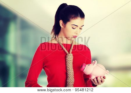 Worried woman holding a piggybank