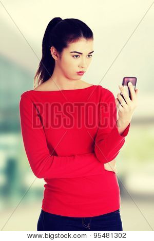 Surprised woman reading text message