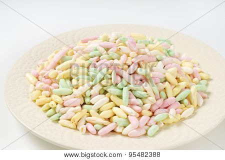 plate of colorful puffed rice on white background