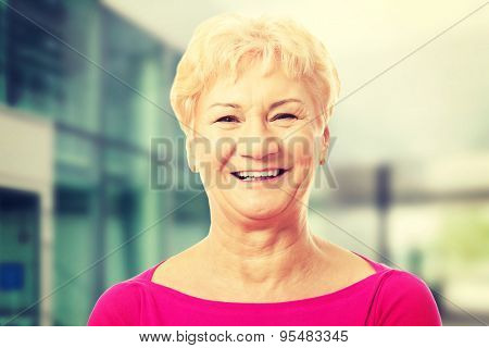 Portrait of an old woman in pink shirt