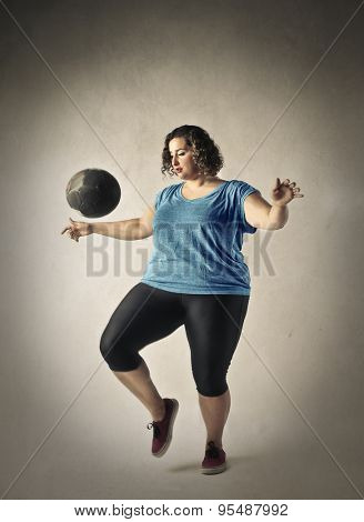 Chubby woman training with a ball