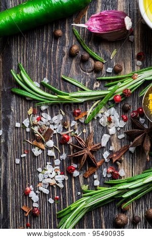 Spices. Herbs and spices selection over wooden background. Pepper, rosemary, salt and garlic.