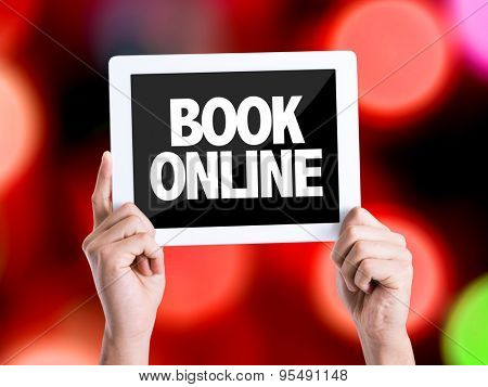 Tablet pc with text Book Online with bokeh background