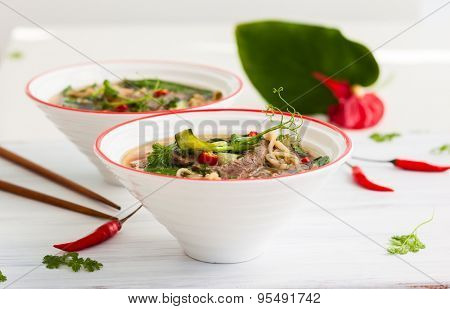 Spicy Asian beef soup with noodles and chinese vegetables