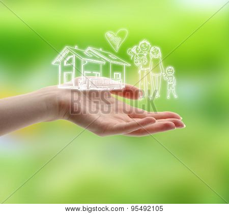 Female hand with drawings of family and house on nature background