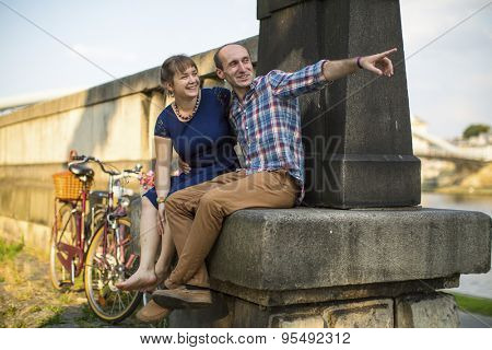 Happy young family. Couple in love sitting on the curb embankment and passionately talking.
