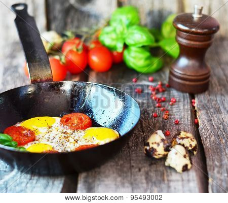 Scrambled eggs with tomatoes and basil in the black pan on the old wooden table