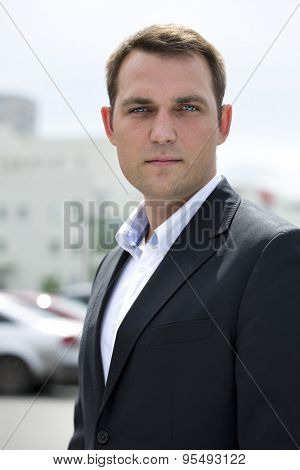 Close-up portrait of a young business man in a dark suit and white shirt on the background of summer city