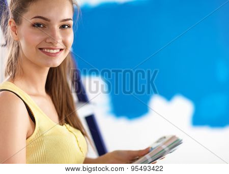 Young beautiful woman holding color palette with color samples.
