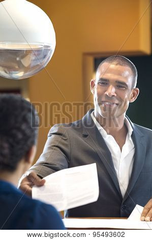 Happy businessman giving paper to receptionist at counter in office