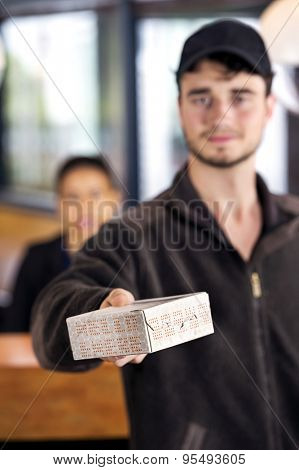Delivery man giving parcel while standing at reception counter in office