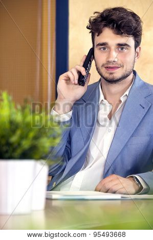Portrait of confident male receptionist using cordless phone at counter in office