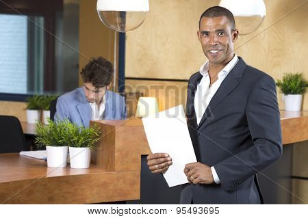 Portrait of confident businessman holding documents while receptionist working at counter in office