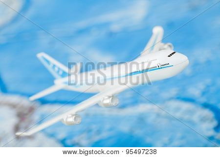 Airplane with world map on background - studio shot