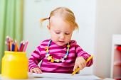 stock photo of daycare  - Adorable happy toddler girl drawing with coloring pencils at home or daycare - JPG