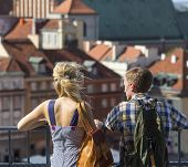 stock photo of observed  - Young couple of tourists looking at the Old European Town from the observation tower - JPG