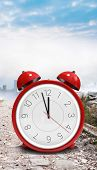 image of count down  - Alarm clock counting down to twelve against stony path leading to misty cityscape - JPG
