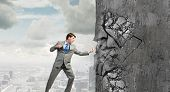 stock photo of karate  - Businessman breaking stone wall with karate punch - JPG