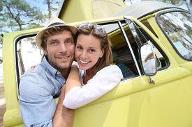 picture of camper  - Couple standing by vintage camper van window - JPG