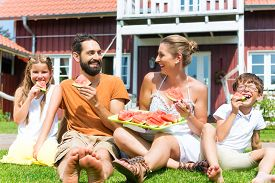 picture of eat grass  - Family sitting in grass in front of house eating water melon to refresh in summer - JPG