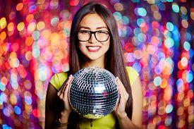 stock photo of posh  - Posh girl with disco ball looking at camera in club - JPG