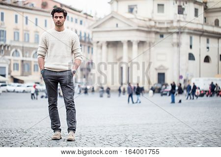 Handsome young man in the city. A handsome young boy is standing on a street in the historic center of Rome in Italy. Hands in his pockets and casual but stylish clothes. Behind him ancient and historical buildings, and a crowd of people and tourists.