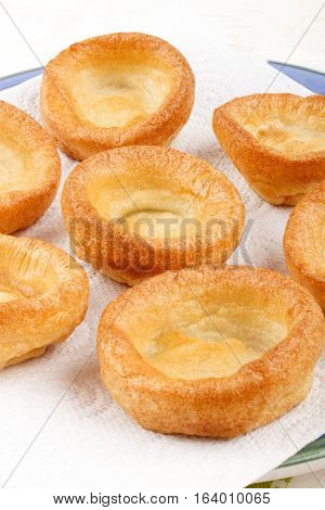 fresh baked yorkshire pudding british food on a plate with white kitchen paper to absorb the oil
