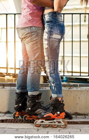 Couple's legs on inline skates. Woman and man in jeans. Sport and style.