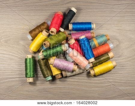 Sewing thread reels on a wood textured background. Bobbins of thread stacked pile.