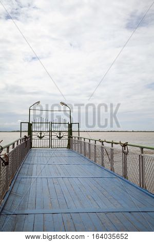 Blue wooden pier with railing. River dock ending with gates decorated with anchors. Horizon and cloudy sky on the background. Quiet, peaceful beautiful view