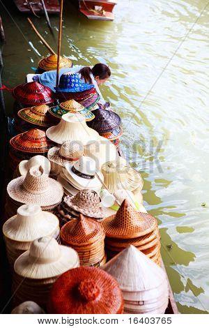 Hat selling on traditional Damnoen Saduak Floating Market near Bangkok in Thailand