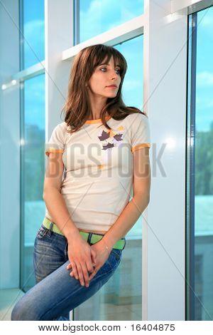 Junge Frau gelehnt Glaswand