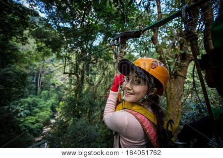 TOURIST adult wearing casual clothes Zip Line On Focus FOREST TRIP fun.