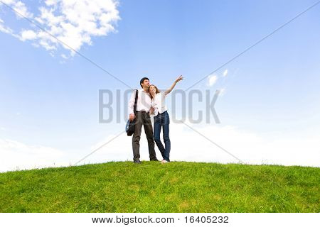 Happy young couple looking at something above a green meadow. Man show something by hand