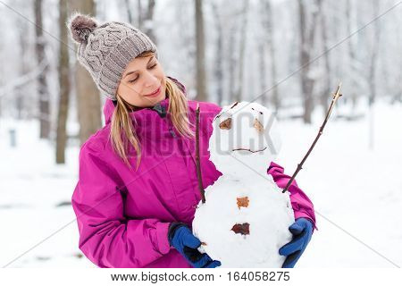 Picture of a beautiful young woman holding a little snowman in her hands