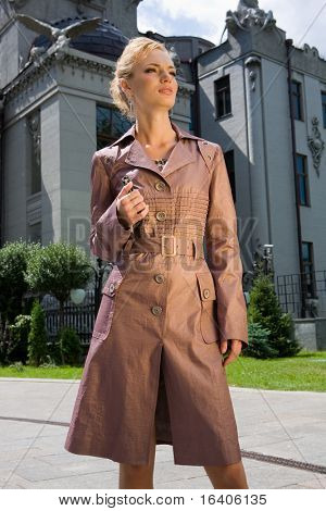 Beautiful Young Woman in brown raincoat. Against the backdrop of against the building.