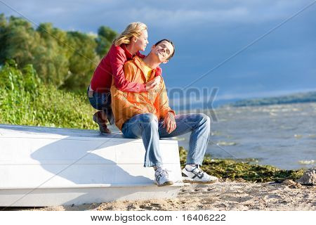 Young love Couple sit on boat on bank of river