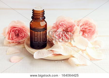 Rose aromatherapy. Essential oil dark glass apothecary dropper bottle, fresh flower petals. Handcrafted botanical beauty care.