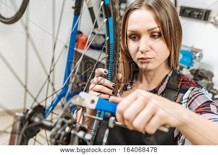 Attentive skilled diligent craftswoman standing in the garage and working while repairing the detail of the bicycle and expressing interest