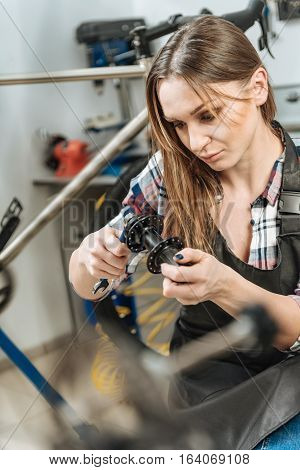 Enjoying the hard work . Concentrated muscular female master standing in the repair shop and working while mending the detail and expressing confidence