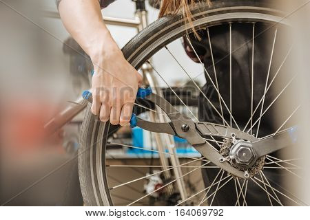 Skillful craftswoman working. Strong athletic masterful craftswoman standing in the workshop and working while fixing the chain of the bicycle and holding different tools