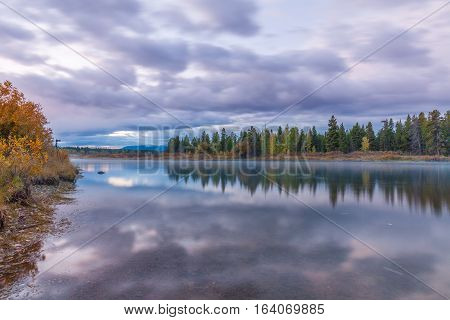 a sunrise reflection in Teton National park in fall